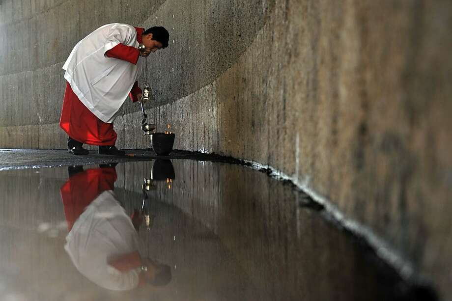 An altar boy prepares coal to fire the incense in the Easter Sunday Mass at the Cathedral of Managua, on March 31, 2013.  AFP PHOTO/Hector RETAMALHECTOR RETAMAL/AFP/Getty Images Photo: Hector Retamal, AFP/Getty Images