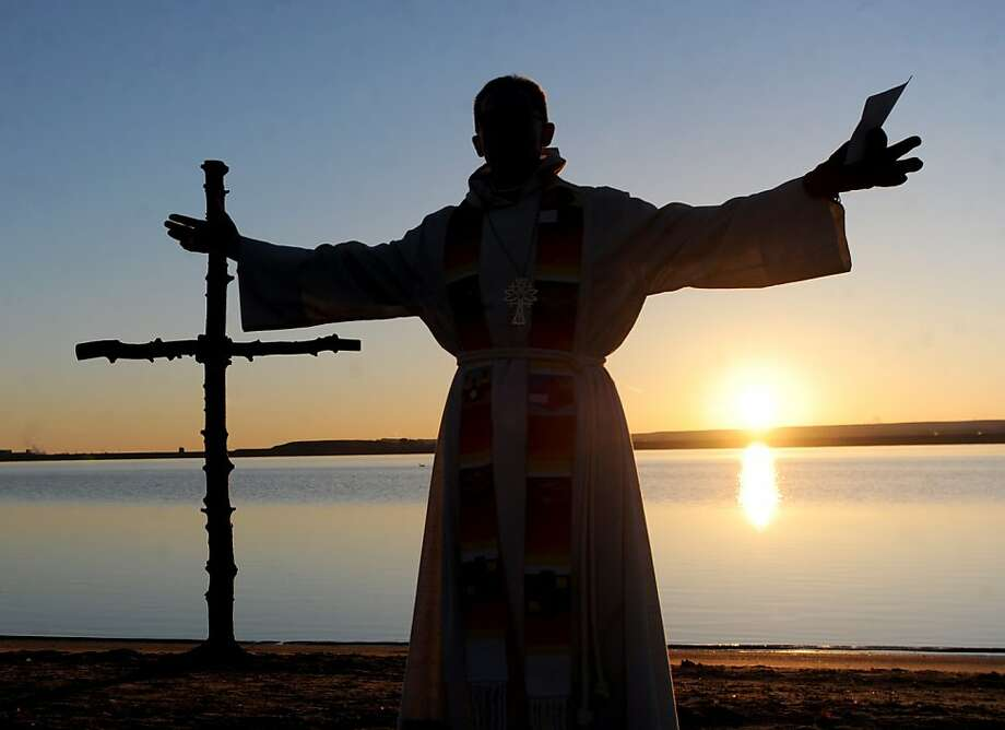 Rev. Mark Twietmeyer,  of Trinity Lutheran Church of Boulder, Colo., delivers his Easter sermon as the sun rises on Sunday, March 31, 2013. Boulder churches, Trinity Lutheran and Shepherd of the Hills Lutheran, celebrated Easter morning with their annual Easter Sunrise Service at the Boulder Reservoir. (AP Photo/Daily Camera, Cliff Grassmick) Photo: Cliff Grassmick, Associated Press