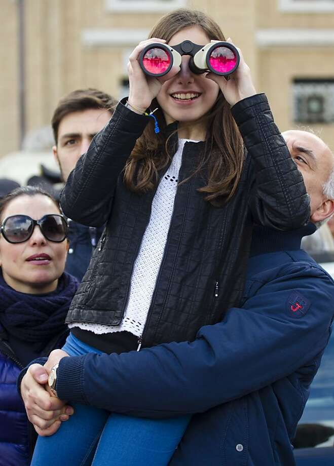 A girl looks through binoculars to follow the Easter Sunday Mass celebrated by Pope Francis, not shown, in St. Peter's Square at the Vatican, Sunday, March 31, 2013. Pope Francis celebrated his first Easter Sunday Mass as pontiff in St. Peter's Square, packed by joyous pilgrims, tourists and Romans and bedecked by spring flowers.Wearing cream-colored vestments, Francis strode onto the esplanade in front of St. Peter's Basilica and took his place at an altar set up under a white canopy. (AP Photo/Domenico Stinellis) Photo: Domenico Stinellis, Associated Press