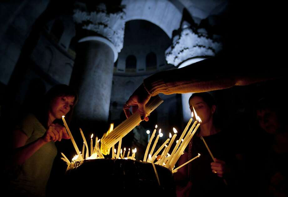 Christian worshippers light candles during the Sunday Easter mass at the Church of the Holy Sepulcher, traditionally believed to be the site of the crucifixion of Christ, in Jerusalem's Old City, Sunday, March 31, 2013. (AP Photo/Sebastian Scheiner) Photo: Sebastian Scheiner, Associated Press