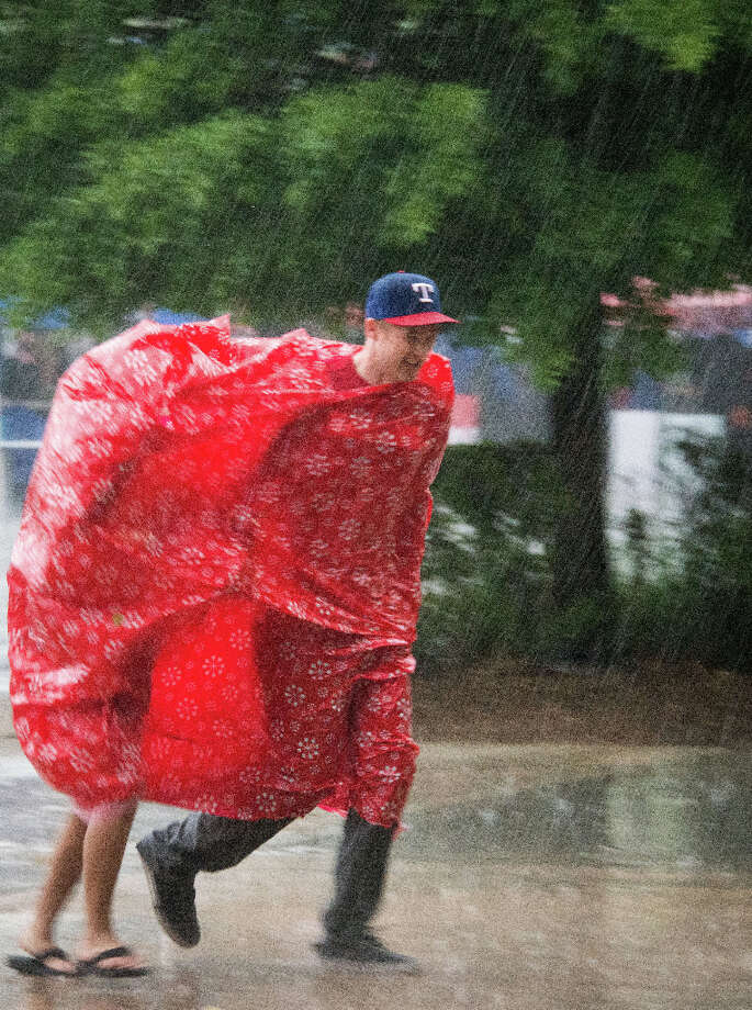 A pair of Rangers fans attempt to stay dry as they run for the stadium in a downpour before the season opener. Photo: Smiley N. Pool, Houston Chronicle / © 2013  Smiley N. Pool