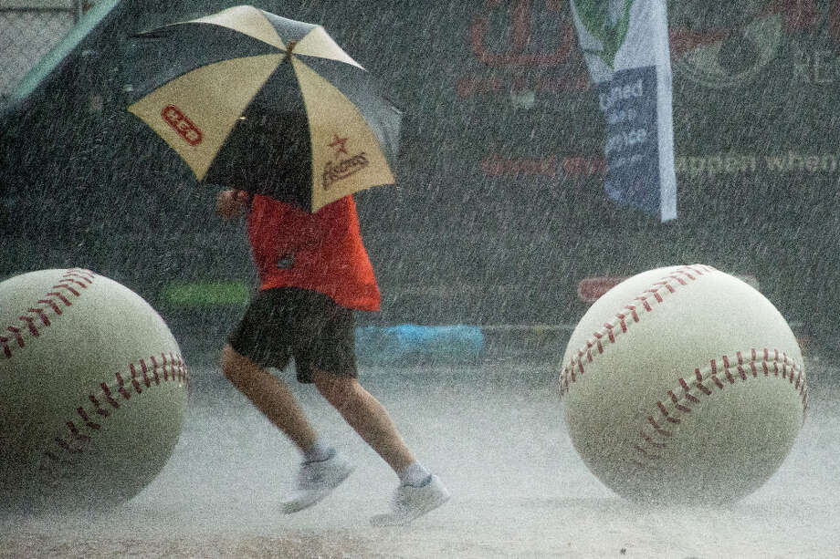 A Astros fan runs for the stadium in a downpour before the season opener against the Rangers. Photo: Smiley N. Pool, Houston Chronicle / © 2013  Smiley N. Pool