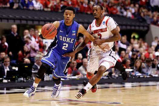 INDIANAPOLIS, IN - MARCH 31:  Quinn Cook #2 of the Duke Blue Devils drives against Russ Smith #2 of the Louisville Cardinals in the second half during the Midwest Regional Final round of the 2013 NCAA Men's Basketball Tournament at Lucas Oil Stadium on March 31, 2013 in Indianapolis, Indiana. Photo: Andy Lyons, Getty Images / 2013 Getty Images