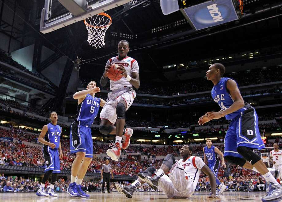 Louisville center Gorgui Dieng (10) comes down with a rebound between Duke's Mason Plumlee (5) and Rasheed Sulaimon, right, during the first half of the Midwest Regional final against Duke in the NCAA college basketball tournament, Sunday, March 31, 2013, in Indianapolis. (AP Photo/Michael Conroy) Photo: Michael Conroy, Associated Press / AP