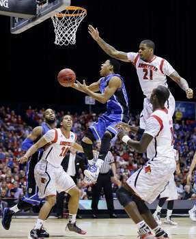 Duke guard Quinn Cook (2) goes up with a shot against Louisville's Chane Behanan (21), Wayne Blackshear (20), and Gorgui Dieng, right, during the first half of the Midwest Regional final in the NCAA college basketball tournament, Sunday, March 31, 2013, in Indianapolis. (AP Photo/Darron Cummings) Photo: Darron Cummings, Associated Press / AP