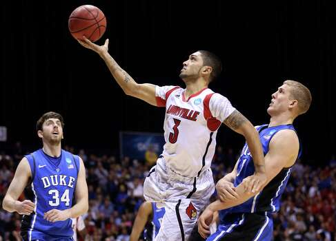 INDIANAPOLIS, IN - MARCH 31:  Peyton Siva #3 of the Louisville Cardinals drives for a shot attempt in the second half against  Ryan Kelly #34 and Mason Plumlee #5 of the Duke Blue Devils during the Midwest Regional Final round of the 2013 NCAA Men's Basketball Tournament at Lucas Oil Stadium on March 31, 2013 in Indianapolis, Indiana. Photo: Streeter Lecka, Getty Images / 2013 Getty Images