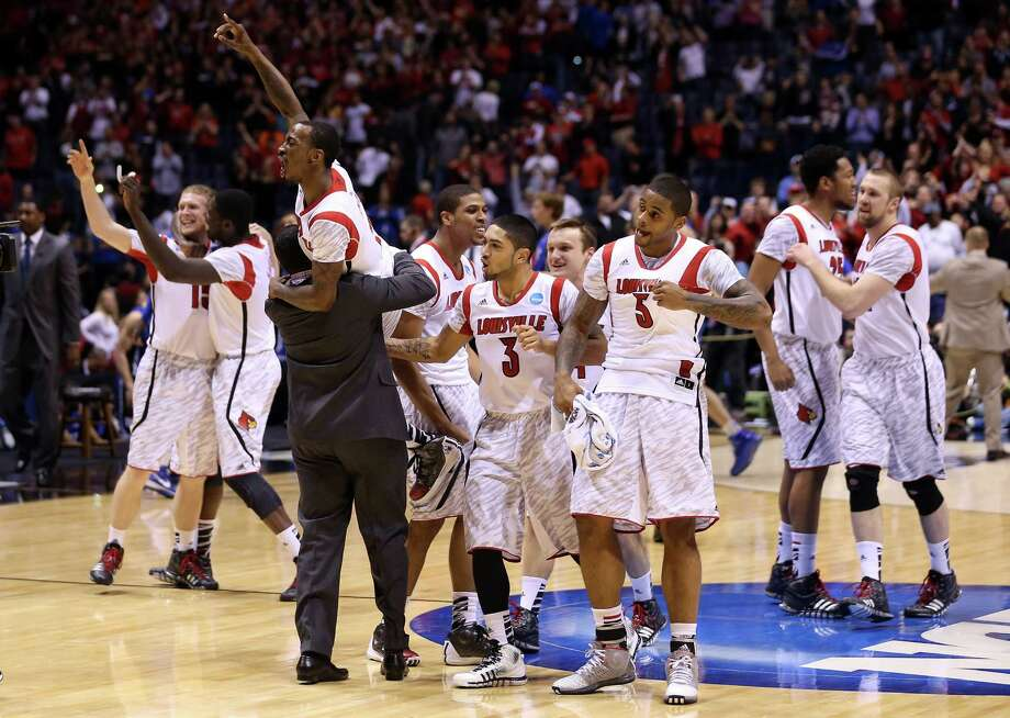 INDIANAPOLIS, IN - MARCH 31:  Russ Smith #2 of the Louisville Cardinals is held up by assistant coach Kevin Keatts as they celebrate with teammates after they won 85-63 against the Duke Blue Devils during the Midwest Regional Final round of the 2013 NCAA Men's Basketball Tournament at Lucas Oil Stadium on March 31, 2013 in Indianapolis, Indiana. Photo: Streeter Lecka, Getty Images / 2013 Getty Images