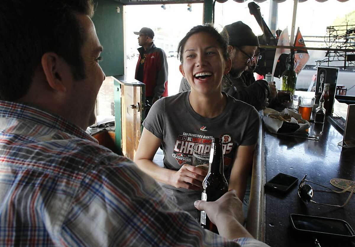 Gary Stephens and Jessica Murayama, enjoy beers before heading off to a Giants game, at the Hotel Utah Saloon on Fourth street in San Francisco, Ca. on Friday Mar. 29, 2013. San Francisco Architectural Heritage has named twenty five legacy bars and restaurants important to the city's cultural scene.