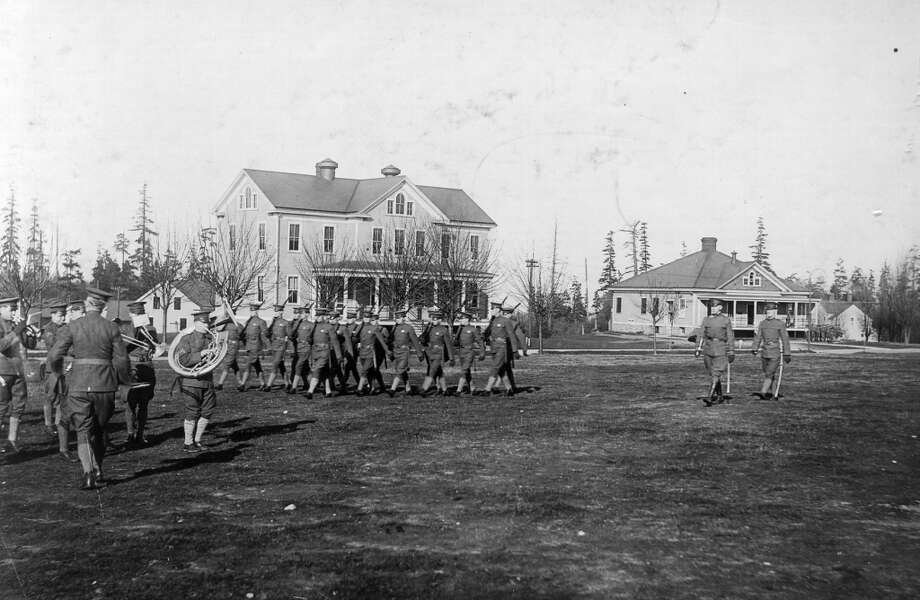 The same buildings - band barracks, left, and guard house - are pictured in 1916 during a U.S. Army drill in Fort Lawton. The city took over the fort in 1970. It's now Discovery Park.