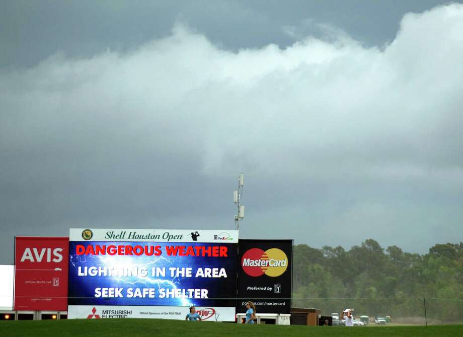 Fans walk off the course past a sign displaying a weather warning message during a delay in the final round of the Houston Open golf tournament, Sunday, March 31, 2013, in Humble, Texas. (AP Photo/Houston Chronicle, Brett Coomer) Photo: Brett Coomer, Associated Press / Houston Chronicle