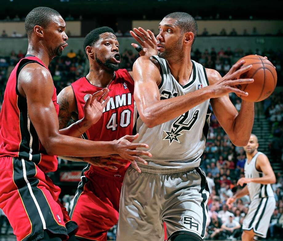 The Spurs' Tim Duncan is defended by Miami Heat's Chris Bosh and Udonis Haslem during first half action Sunday, March 31, 2013 at the AT&T Center. Photo: Edward A. Ornelas, San Antonio Express-News / © 2013 San Antonio Express-News