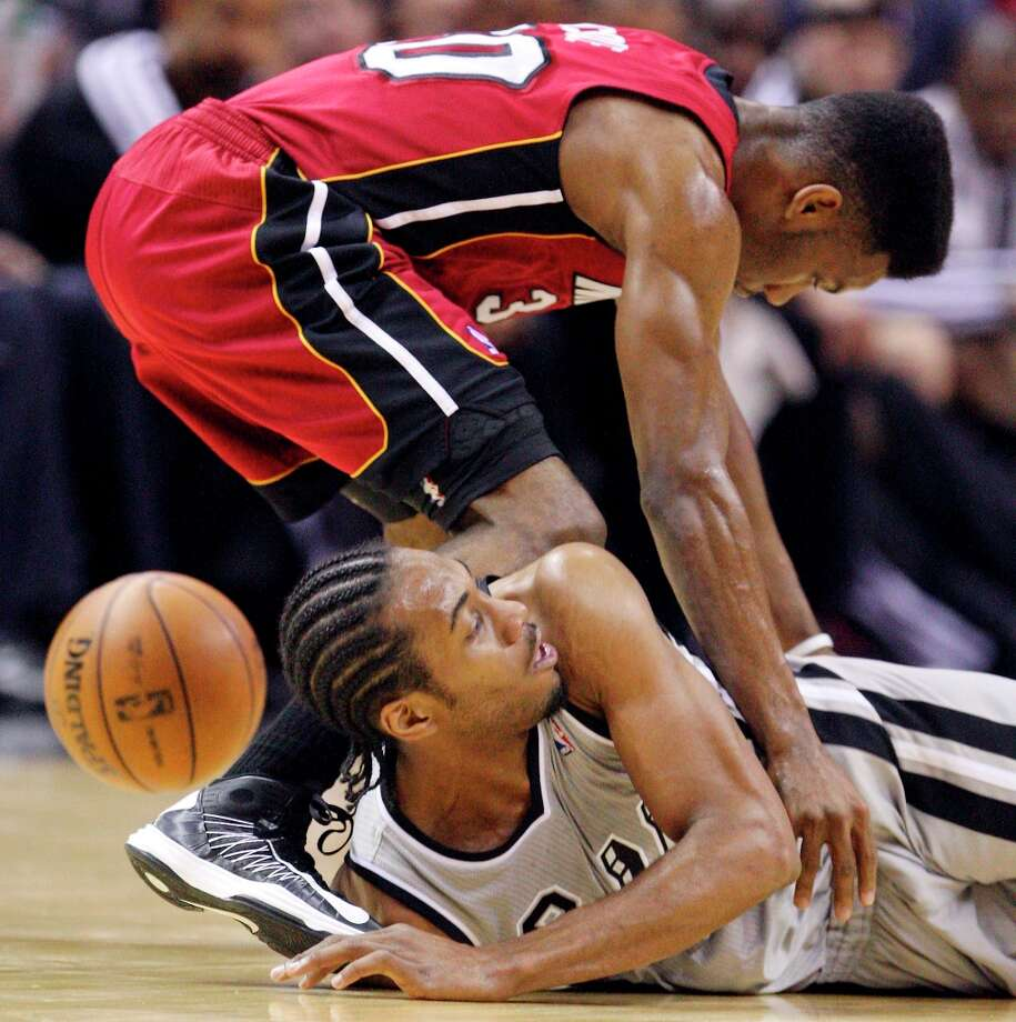 The Spurs' Kawhi Leonard and Miami Heat's Norris Cole grab for a loose ball during first half action Sunday, March 31, 2013 at the AT&T Center. Photo: Edward A. Ornelas, San Antonio Express-News / © 2013 San Antonio Express-News