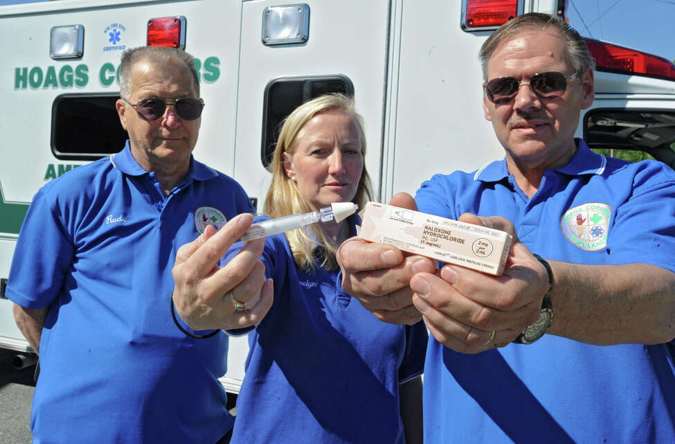 Driver Rudy Jahn stands with EMTs Carolyn Fleming and Paul Glasser who are holding the drug Naloxone Hydrochloride at the Hoags Corners ambulance garage Friday, May 18, 2012 in East Nassau, N.Y. The Hoags Corners EMTs are the first in a pilot program that allows EMTs to administer a drug that can reverse an opioid overdose. (Lori Van Buren / Times Union)