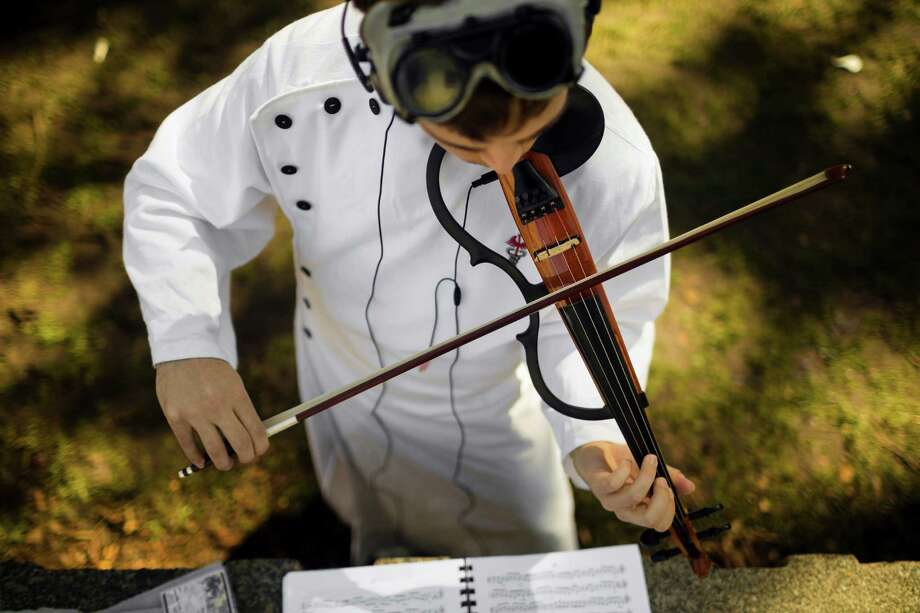 "Alex Wilkens, 20, dressed as ""Doctor Horrible,"" practices his instrument in the sunlight outside of the 16th annual Sakura-Con Sunday, March 31, 2013, at the Washington State Convention Center in Seattle. Presented by the Asia Northwest Cultural Education Association, Sakura-Con featured three days of anime theaters, gaming, cosplay, cultural panels, dances, concerts, art contests and industry guests. Photo: JORDAN STEAD / SEATTLEPI.COM"