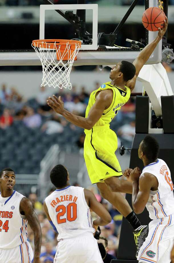 Michigan's Glenn Robinson III catches Florida's Michael Frazier II (20) and Will Yeguete, right, flat-footed in much the same way the Wolverines soared past the Gators on Sunday. Photo: Tony Gutierrez, STF / AP