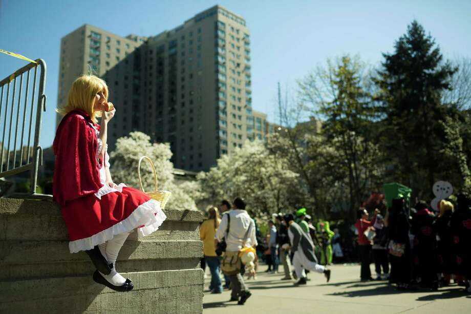 Claire Hankin, 13, from San Francisco and dressed as Rin Kagamine, enjoys an apple outside from her perch at the 16th annual Sakura-Con Sunday, March 31, 2013, at the Washington State Convention Center in Seattle. Presented by the Asia Northwest Cultural Education Association, Sakura-Con featured three days of anime theaters, gaming, cosplay, cultural panels, dances, concerts, art contests and industry guests. Photo: JORDAN STEAD / SEATTLEPI.COM