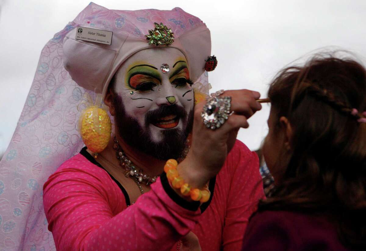 Sister Tatiana from the Sisters of Perpetual Indulgence does Kenza-Luma Hamilton's face paint at the 2013 Dolores Park Easter Celebration on March 30th, 2013 in San Francisco, Calif.