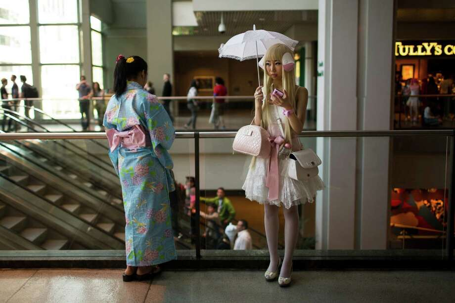 Yumi King, 22, right, texts friends while taking a break from the 16th annual Sakura-Con Sunday, March 31, 2013, at the Washington State Convention Center in Seattle. Presented by the Asia Northwest Cultural Education Association, Sakura-Con featured three days of anime theaters, gaming, cosplay, cultural panels, dances, concerts, art contests and industry guests. Photo: JORDAN STEAD / SEATTLEPI.COM