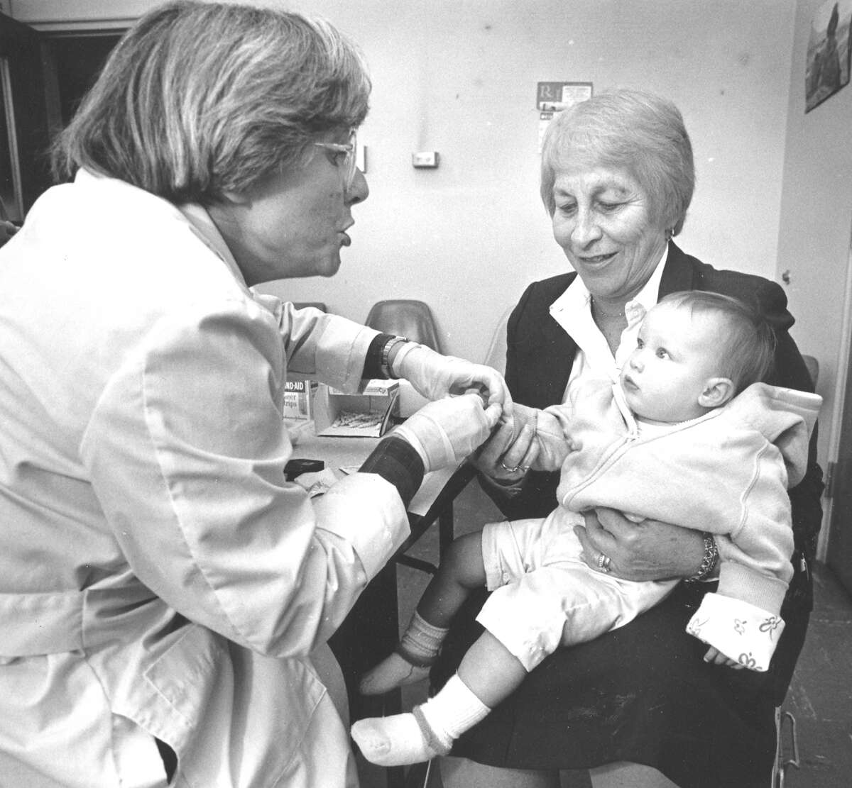 Lee Stoogenke, a lab technician for the Stamford Health Department, does a blood test on 9-month-old Sheila Coperine, whose mother was a teacher at K.T. Murphy School, which was closed due to high lead levels. Holding Sheila is Springdale School nurse Estelle Skigen.