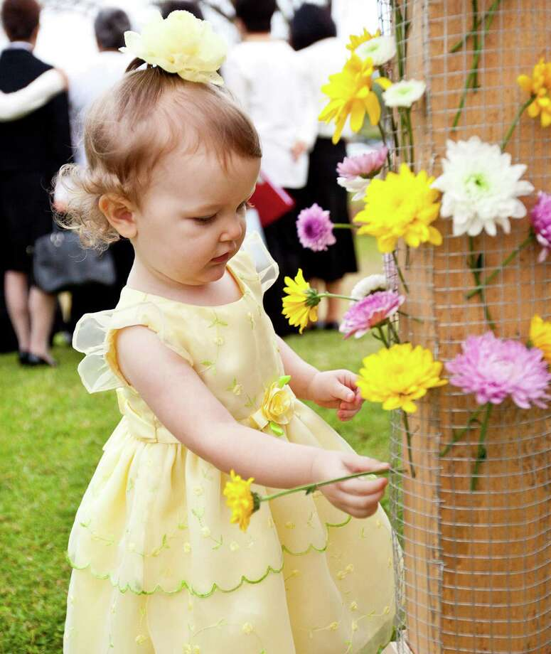 Shylee House, 19 months, puts flowers on a cross at Spring Valley Park after the sunrise celebration. Photo: Nick De La Torre, Staff / © 2013 Houston Chronicle