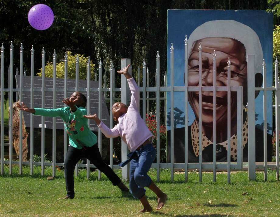 Children play ball in front of a giant portrait of former president Nelson Mandela in a park in Soweto, South Africa, Sunday, March 31, 2013. Mandela remains in a hospital while he receives treatment for a recurrence of pneumonia. Presidential spokesman Mac Maharaj says there are no updates on 94 year old Mandela since an official statement Saturday on his condition. That statement reported the anti-apartheid leader was breathing without difficulty after having a procedure to clear fluid in his lung area. (AP Photo/Denis Farrell) Photo: Denis Farrell