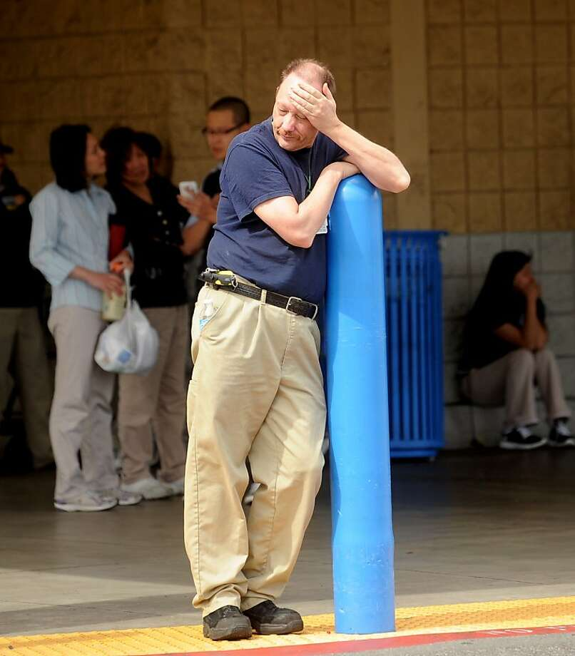 A Walmart worker, who declined to give his name, waits outside a Walmart in San Jose, Calif., after a motorist drove through a store entrance and began assaulting shoppers on Sunday, March 31, 2013. Four people sustained injuries during the attack according to a police spokesman. (AP Photo/Noah Berger) Photo: Noah Berger, Associated Press