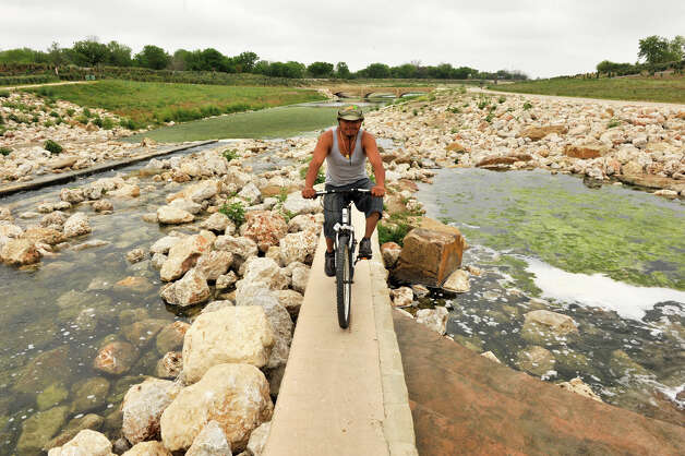 Israel Rodriguez rides his bike on a recently completed portion of the Mission Reach at Padre Park Sunday morning, March 31, 2013. Photo: Robin Jerstad, For The San Antonio Express-News