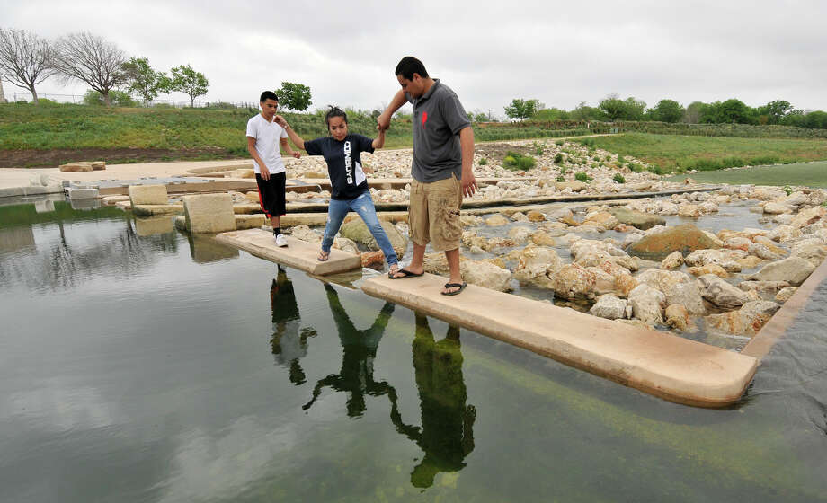 George Estala (from left), Roxanne Estala and Eduardo Fuentes, explore the recently completed portion of the Mission Reach section at Padre Park Sunday morning, March 31, 2013. Photo: Robin Jerstad, For The San Antonio Express-News