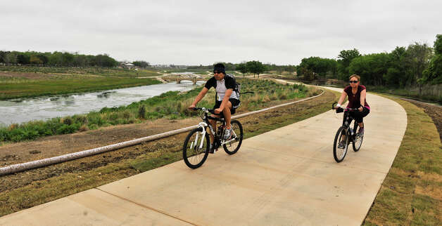 David and Idalia Hernandez bike along a recently completed section of the Mission Reach near Padre Park Sunday morning, March 31, 2013. Photo: Robin Jerstad, For The San Antonio Express-News