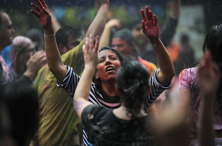 """Revellers covered in coloured powders and water celebrate """"Holi"""" in Hong Kong on March 31, 2013. Holi, the festival of colours where people smear each other with coloured powder and water, is celebrated by Hindus across the world.       AFP PHOTO / ANTHONY WALLACEANTHONY WALLACE/AFP/Getty Images Photo: Anthony Wallace, AFP/Getty Images"""