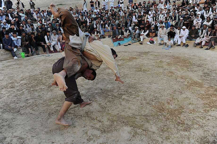 Afghan wrestlers compete in an impromptu ring arena in a field in the northern town of Mazar-i-Sharif in Balkh province on March 30, 2013. Wrestling is very popular and it is traditionally practiced by the poorer Afghans. AFP PHOTO/ Farshad UsyanFARSHAD USYAN/AFP/Getty Images Photo: Farshad Usyan, AFP/Getty Images