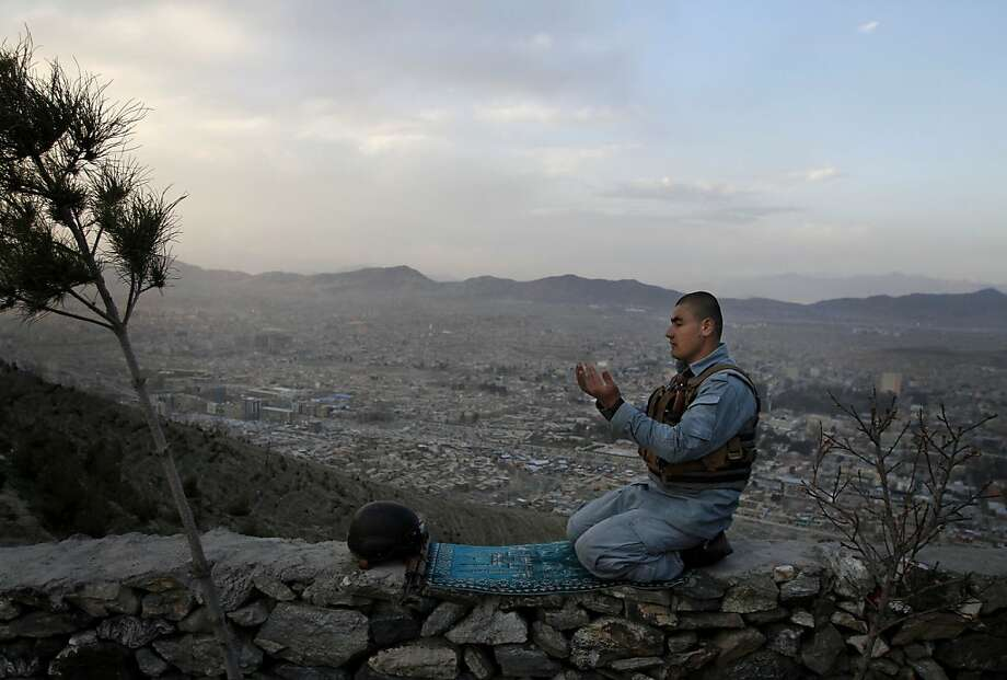 An Afghan police man offers evening prayers on a hill overlooking Kabul, Afghanistan, Sunday, March 31, 2013. Afghan President Hamid Karzai held talks Sunday with the Emir of Qatar during a visit to discuss opening a Taliban office in the Gulf state, as a prelude to possible peace negotiations with the militants. (AP Photo/Ahmad Jamshid) Photo: Ahmad Jamshid, Associated Press