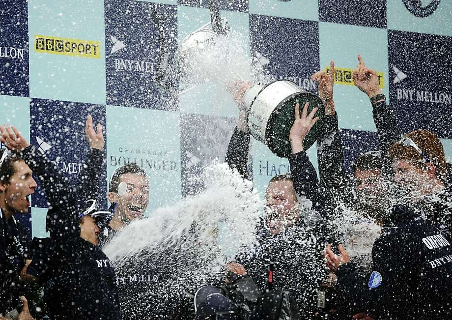 The Oxford University boat crew celebrate with the trophy on the podium after beating the Cambridge University crew during the annual boat race on the River Thames in London on March 31, 2013. Oxford won the 159th Annual boat race between Oxford University and Cambridge University. AFP PHOTO / ADRIAN DENNISADRIAN DENNIS/AFP/Getty Images Photo: Adrian Dennis, AFP/Getty Images