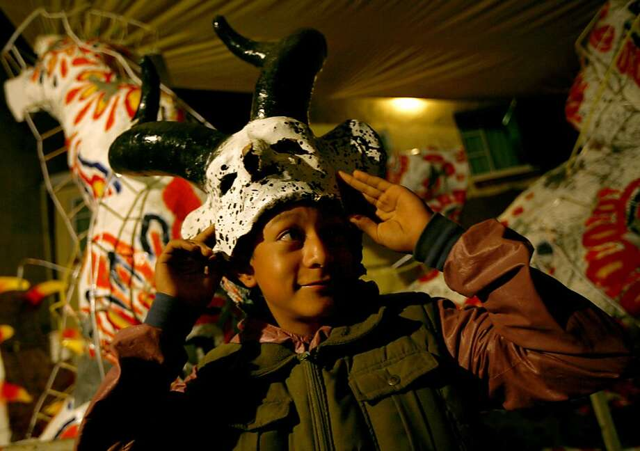 A young boy wears a mask of the devil prior to the burning of a giant 5-meter tall devil-like figure representing Judas in the atrium of the Santa Rosa Xochiac church, in Mexico City,  Sunday, March 31, 2013. The Burning of Judas is an Easter-time ritual in many communities, where an effigy of Judas Iscariot is hanged on Good Friday, then burned on Easter Sunday. (AP Photo/Marco Ugarte) Photo: Marco Ugarte, Associated Press