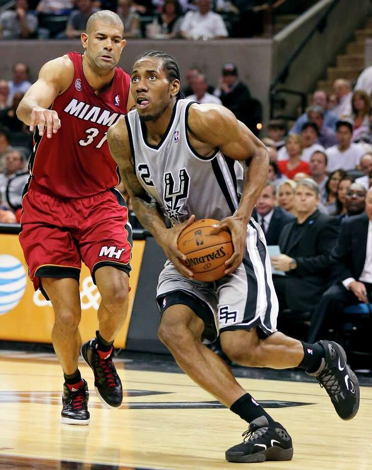 The Spurs' Kawhi Leonard drives to the basket around Miami Heat's Shane Battier during second half action Sunday, March 31, 2013 at the AT&T Center. The Heat won 88-86. Photo: Edward A. Ornelas, San Antonio Express-News / © 2013 San Antonio Express-News