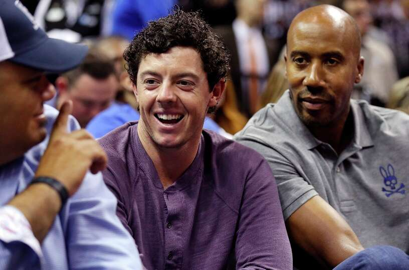 Pro golfer Rory McIlroy (center) sits with former Spurs player Bruce Bowen during the Spurs and Heat
