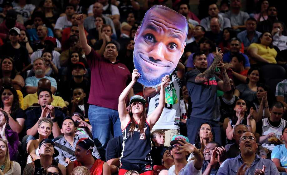 A Miami Heat fan holds a cutout of LeBron James' face during second half action of the Heat and Spurs game Sunday, March 31, 2013 at the AT&T Center. The Heat won 88-86. Photo: Edward A. Ornelas, San Antonio Express-News / © 2013 San Antonio Express-News