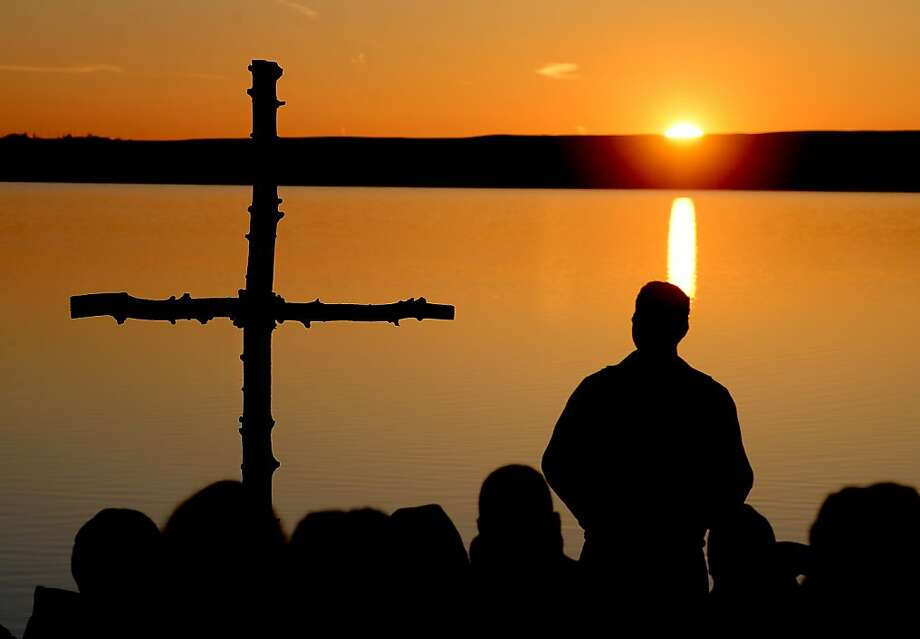 Rev. Martin Lettow, of Shepherd of Hills Lutheran Church of Boulder, Colo., delivers his sermon as the sun rises over the reservoir. Boulder churches, Trinity Lutheran and Shepherd of the Hills Lutheran, celebrated Easter morning with their annual Easter Sunrise Service at the Boulder Reservoir on March 31, 2013. (AP Photo/Daily Camera, Cliff Grassmick) Photo: Cliff Grassmick, Associated Press