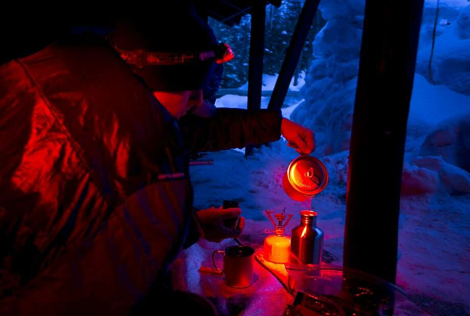 A climber pours steaming water into a bottle that he will use to keep his sleeping bag warm while camping in a lean-to at Hermit Lake, Friday evening, March 29, 2013, on the slopes of Mt. Washington in New Hamsphire.(AP Photo/Robert F. Bukaty) Photo: Robert F. Bukaty, Associated Press