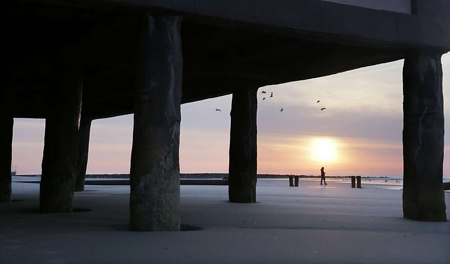 A person walks along the beach near the Music Pier building in Ocean City, N.J., as the sun comes up Easter morning, Sunday, March 31, 2013. (AP Photo/Mel Evans) Photo: Mel Evans, Associated Press