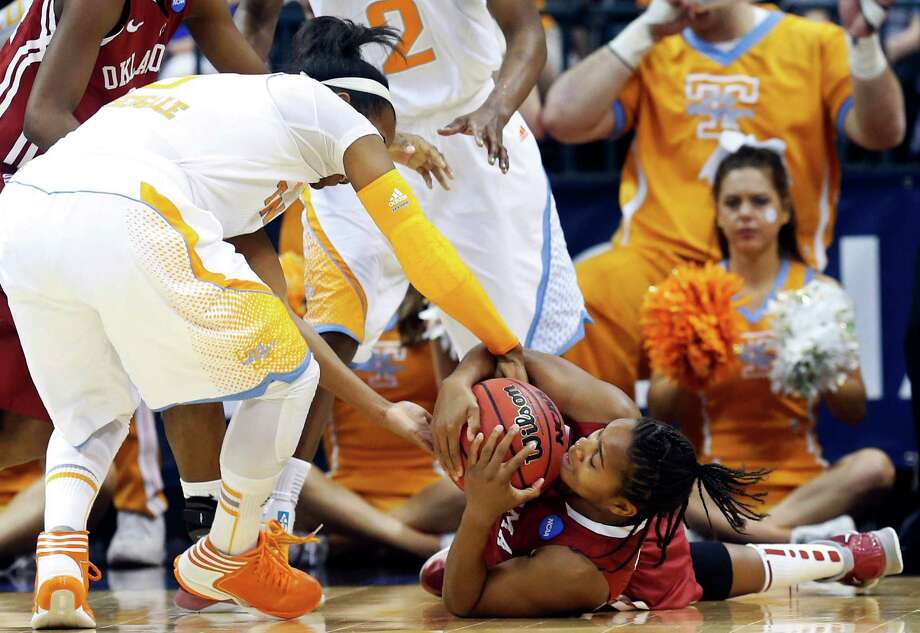 Tennessee guard Kamiko Williams, left, and Oklahoma guard Jasmine Hartman, right, fight for control on the ball in the first half of a regional semifinal in the women's NCAA college basketball tournament in Oklahoma City, Sunday, March 31, 2013. (AP Photo/Sue Ogrocki) Photo: Sue Ogrocki