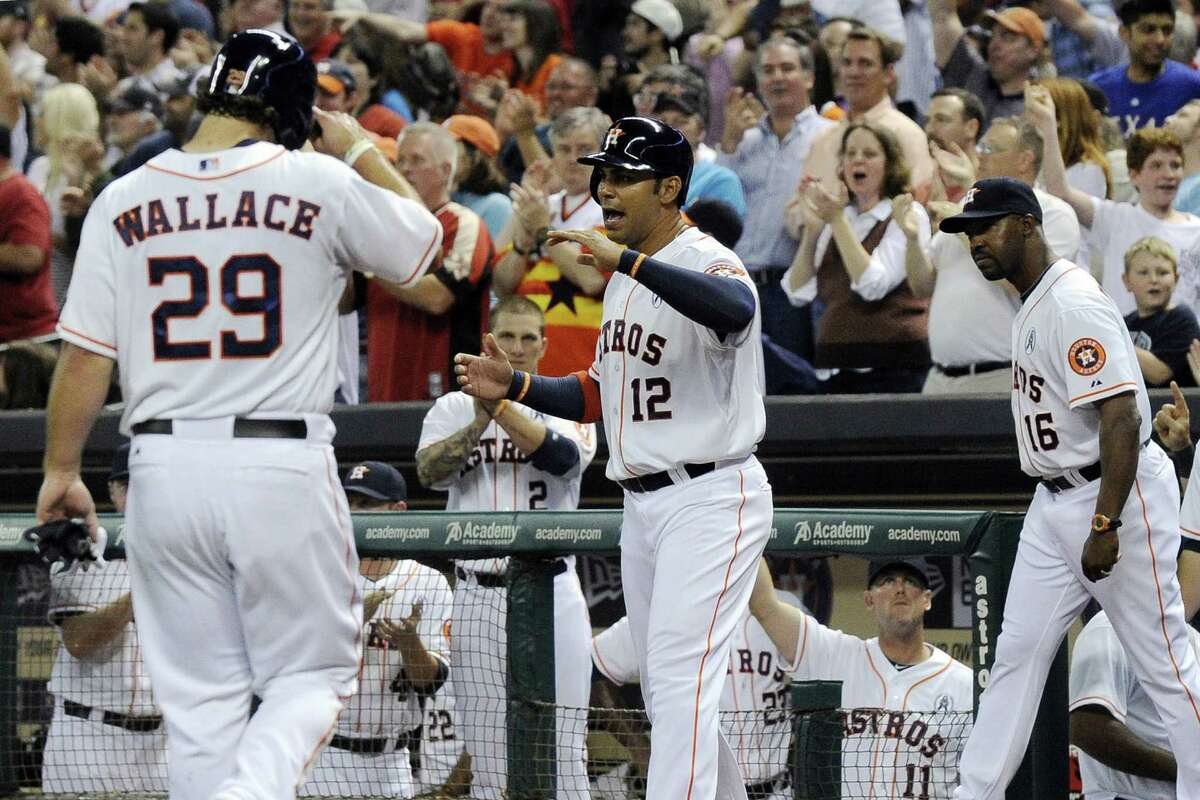 Carlos Pena (12) of the Astros welcomes Brett Wallace to the dugout after the two scored on Justin Maxwell's two-run triple in the fourth inning of Sunday's win.