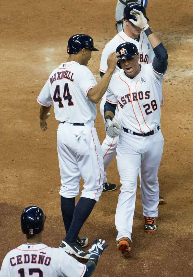 Pinch hitter Rick Ankiel (28) celebrates with third baseman Matt Dominguez, top, and center fielder Justin Maxwell (44) after Ankiel's three-run homer in the sixth inning gave the Astros a five-run lead over the Rangers on Sunday. Photo: Smiley N. Pool / © 2013  Smiley N. Pool