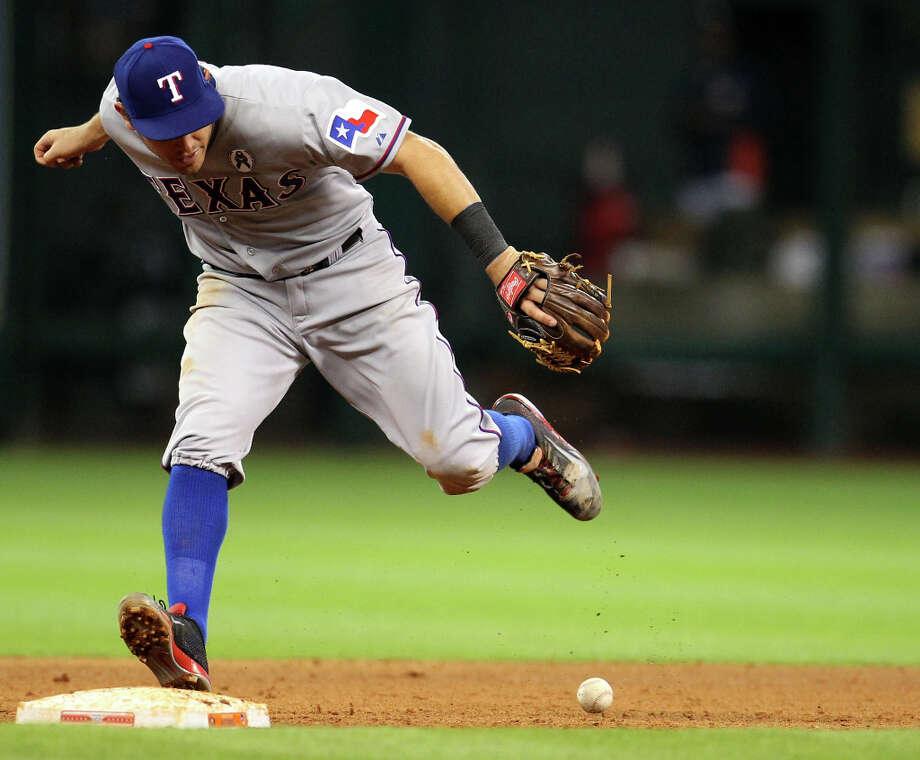 Rangers second baseman Ian Kinsler bobbles a ground hit by Astros third baseman Matt Dominguez during the eighth inning. Photo: Karen Warren, Houston Chronicle / © 2013 Houston Chronicle