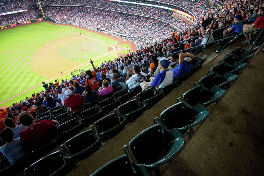 Plenty of empty seats can be found in the upper deck as second baseman Jose Altuve singles to lead off bottom of the first inning. It was the first hit by the Astros as an American League team. Photo: Smiley N. Pool, Houston Chronicle / © 2013  Smiley N. Pool