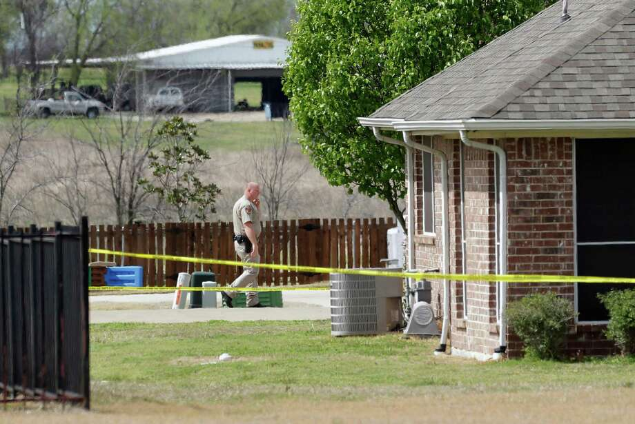 A Kaufman County Sheriff's deputy walks near the taped-off property of Kaufman County District Attorney Mike McLelland, near Forney, Texas, on Sunday, March 31, 2013. On Saturday, McLelland and his wife, Cynthia, were murdered in their home. Photo: Mike Fuentes