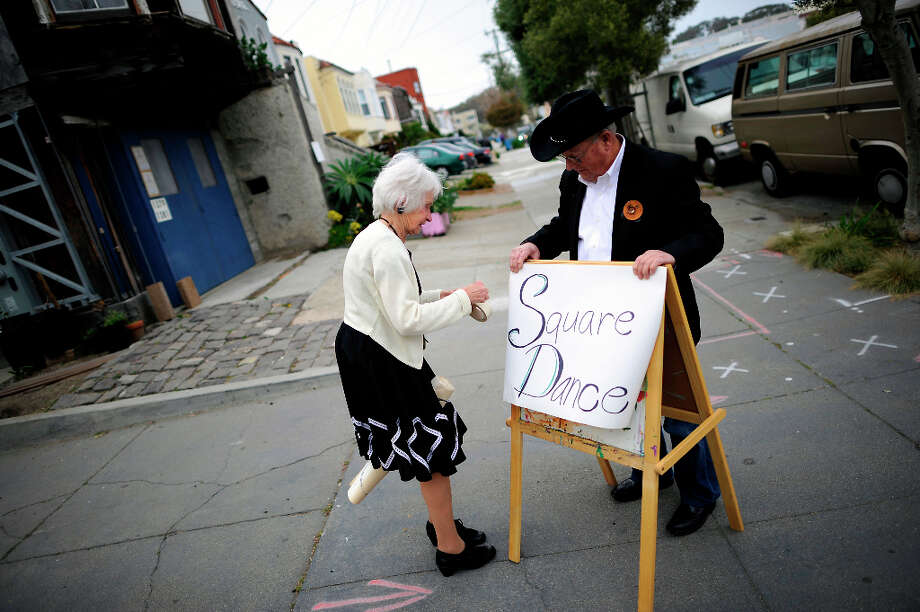 Caper Cutters president Barbara Styles and 49ers(dance club) president Bill Avants set up a sign on the sidewalk announcing the weekly sguare dance.  The Caper Cutters Square Dancing Club hosted their weekly dance and beginners lessons at St. Paul's Church in the Sunset District of San Francisco, Monday March 11th, 2013. Photo: Michael Short, Special To The Chronicle / ONLINE_YES