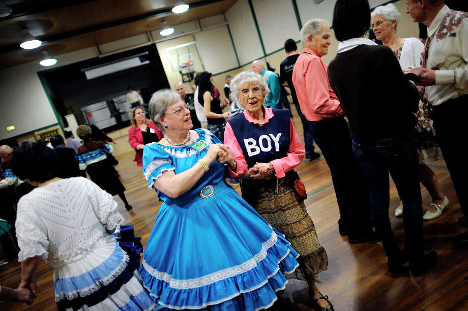 Donna Campbell(L) promenades with the oldest member of the group Barbara Johnson, 91, who is wearing a bib marked BOY to make up for the disproportionate ratio of women to men dancers.  The Caper Cutters Square Dancing Club hosted their weekly dance and beginners lessons at St. Paul's Church in the Sunset District of San Francisco, Monday March 11th, 2013. Photo: Michael Short, Special To The Chronicle / ONLINE_YES