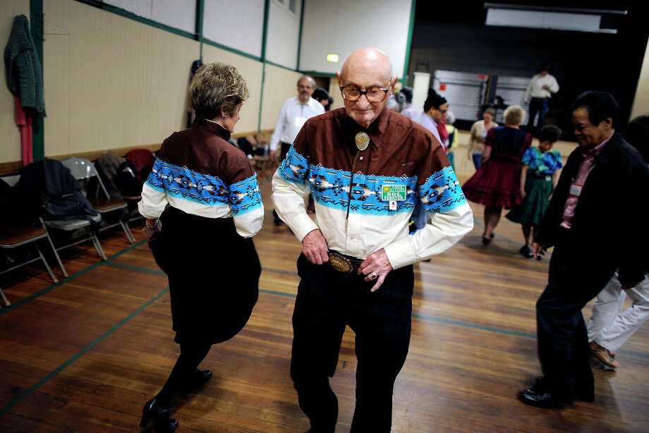 Wearing matching shirts, Sol Fenster(R) and his partner Connie Maracle go round and round with their group of dancers. The Caper Cutters Square Dancing Club hosted their weekly dance and beginners lessons at St. Paul's Church in the Sunset District of San Francisco, Monday March 11th, 2013. Photo: Michael Short, Special To The Chronicle / ONLINE_YES