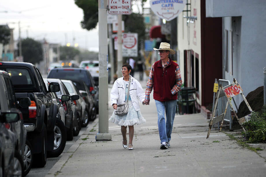 Alice Chan and Ed Patterson of San Francisco walk up Judah St. on their way to the Square Dance.  The Caper Cutters Square Dancing Club hosted their weekly dance and beginners lessons at St. Paul's Church in the Sunset District of San Francisco, Monday March 11th, 2013. Photo: Michael Short, Special To The Chronicle / ONLINE_YES